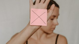 woman hand up with x on post it